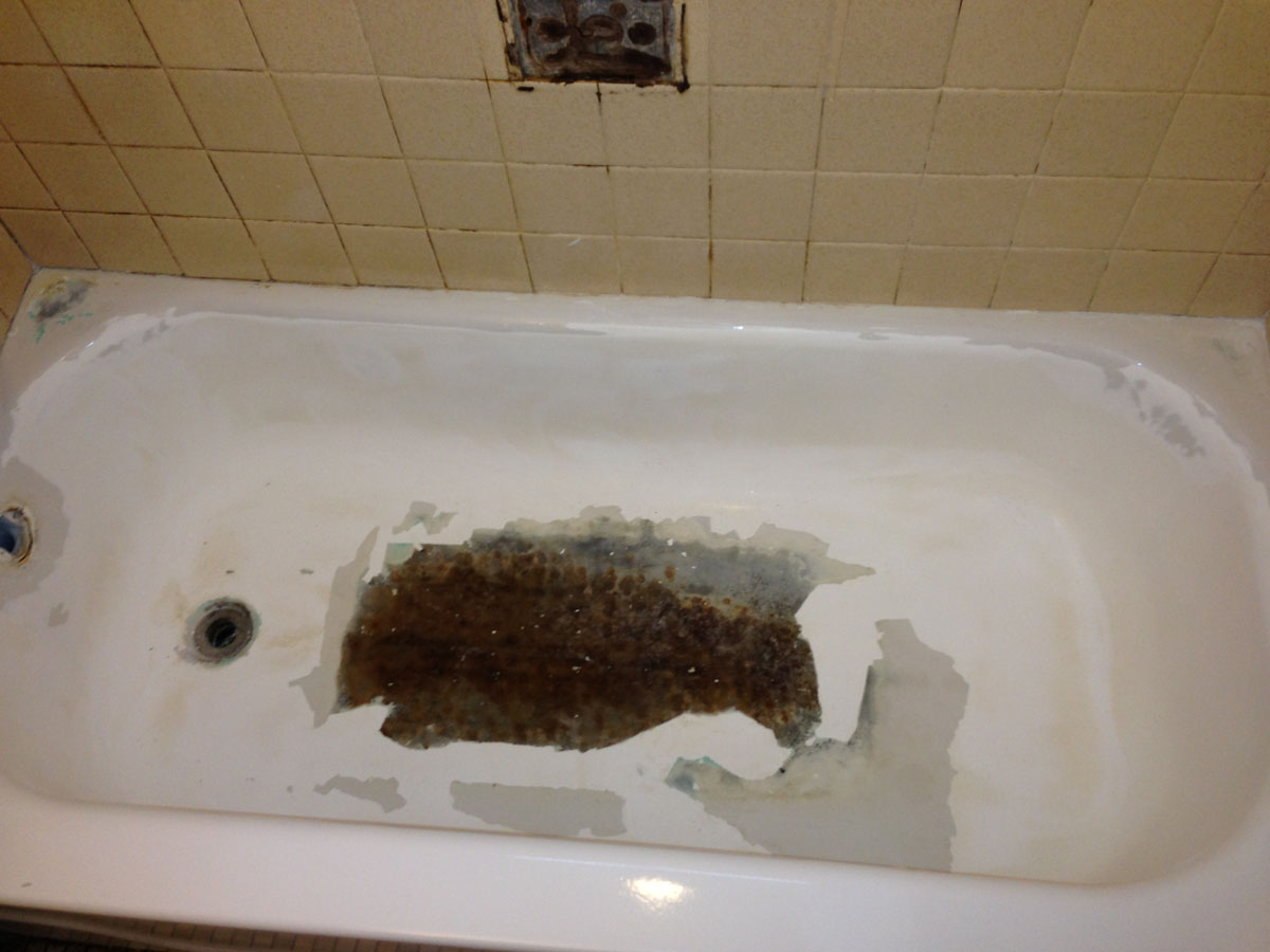 Bathtub with large rusty deglazed area before refinishing