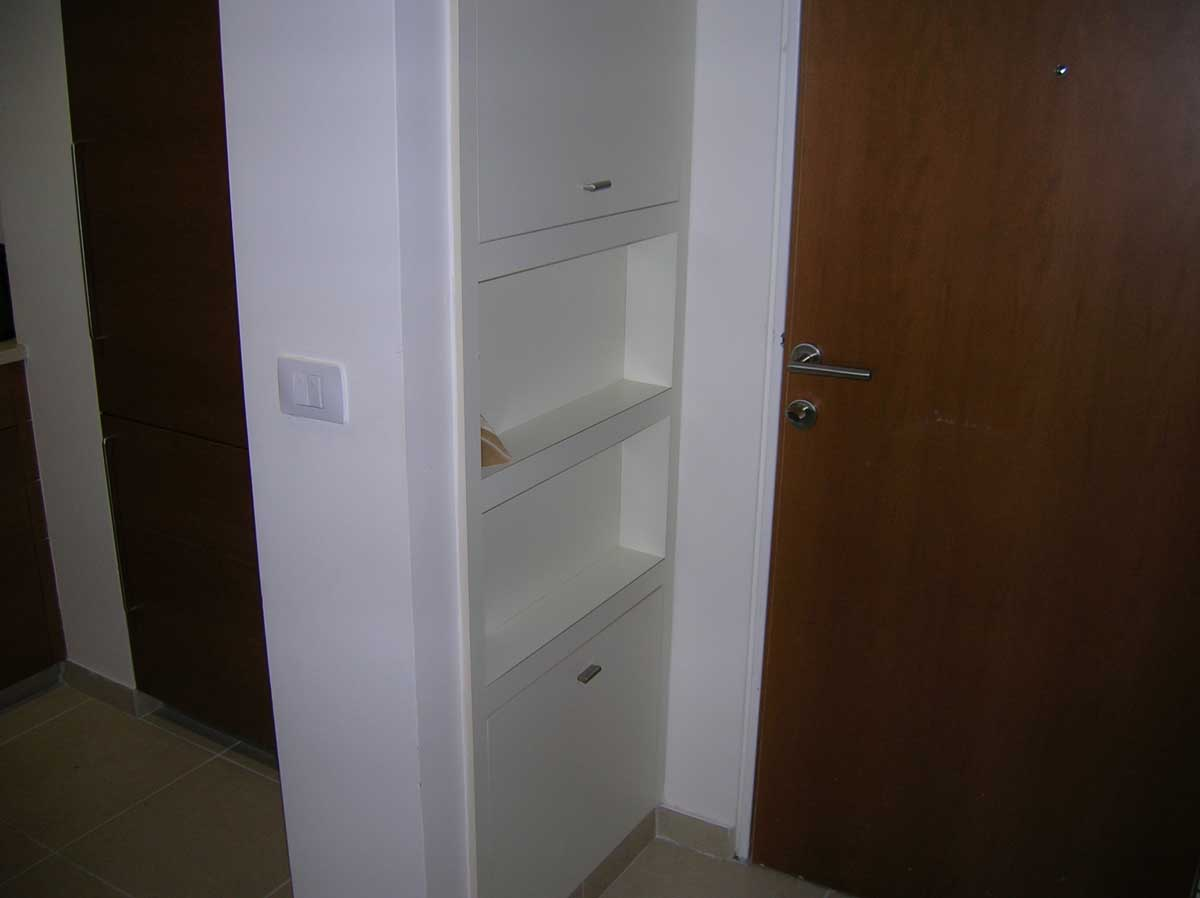 Custom shelves and cabinets in living room door niche - Arlington kitchen remodel by Bay State