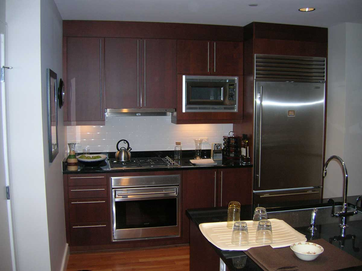 Remodeled kitchen - dark wood cabinets with stainless hardware