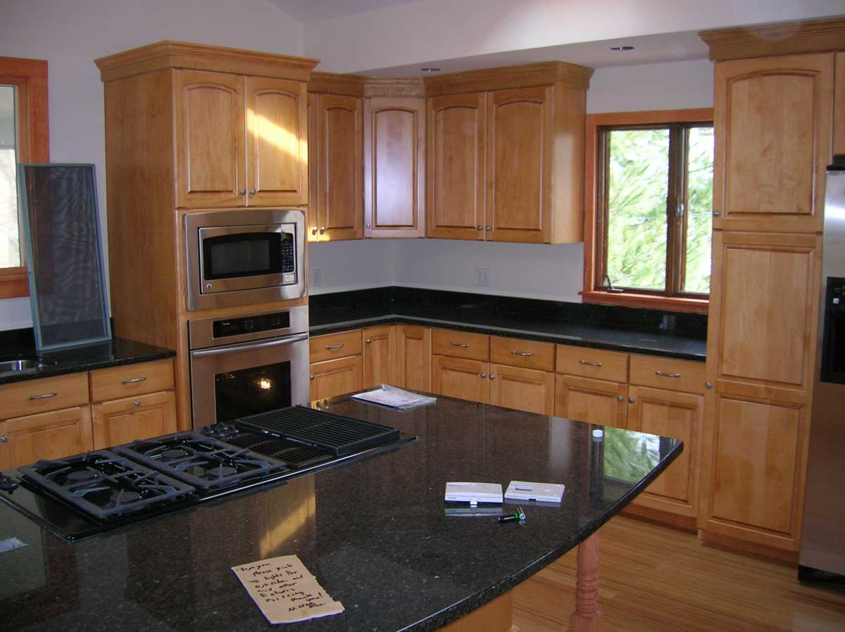 Gorgeous wood cabinets and granite countertops in Brookline kitchen remodel by Bay State Refinishing
