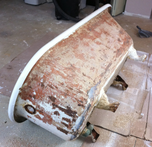 Heavily rusted antique cast iron bathtub before refinishing