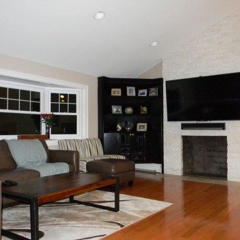 Newton living room remodel - showing bay window, builit-in corner book shelving, and new floor to ceiling fireplace facade